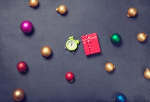 Gift and alarm clock with baubles on grey background